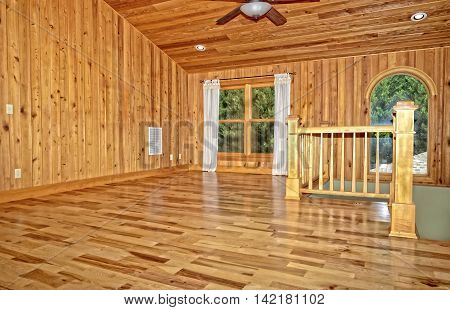 An empty room with hickory floors, cypress walls and ceiling.