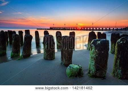 Old piles of breakwater on Baltic coast over the sunrise.