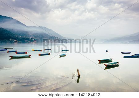 Boats on Phewa Lake in Pokhara, three sunken ones in the foreground, Nepal.
