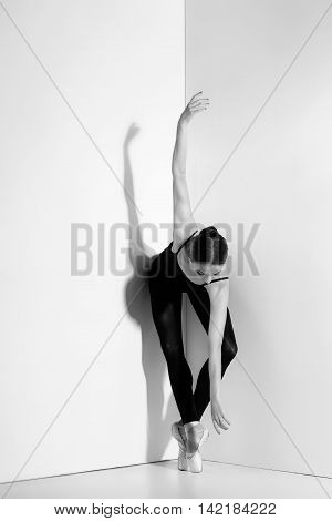 Ballerina in black outfit posing on pointe shoes, studio gray background.