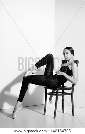 Ballerina in black outfit posing on on a wooden chair, studio gray background.