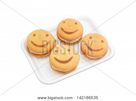 Several flaky biscuit with the image of smiling face made of inserts of jam on a plastic tray on a light background