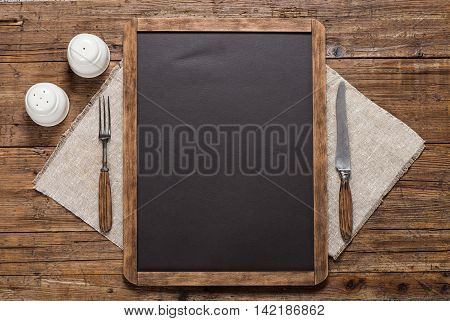 Blackboard for your text spices vintage spoon and fork on linen napkin on a rustic wooden table Top view with copy space.
