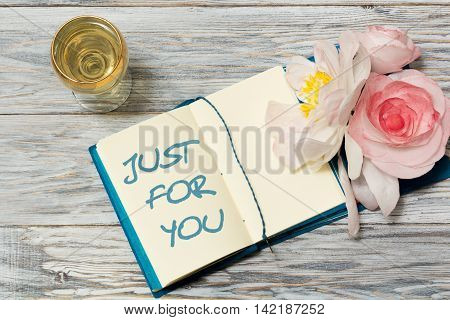 Glass of white wine and text in Notepad: Just for you. Closeup
