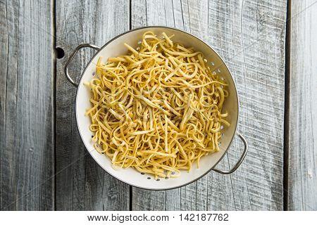 Tasty spaetzle pasta in colander.
