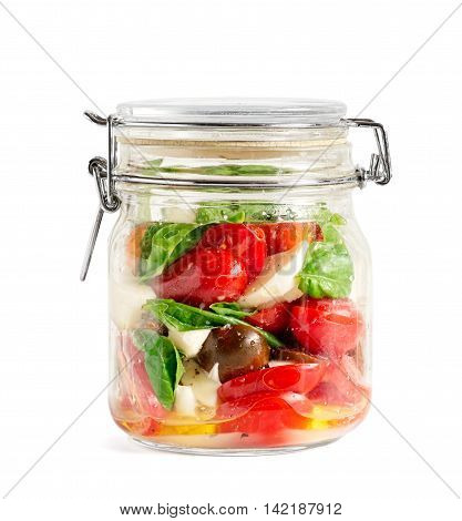 Mixed caprese salad in a closed lid glass mason jar isolated on white
