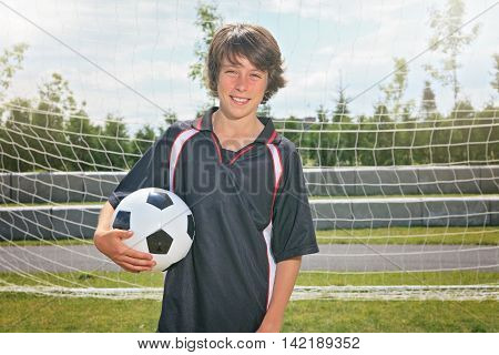 A soccer player on the play field. The boy hold a ball.