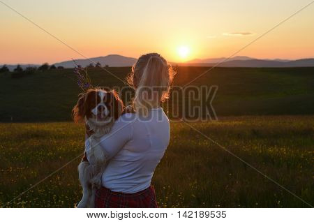 Woman holding her Cavalier King Charles Spaniel Blenheim dog and looking at hills in landscape in sunset