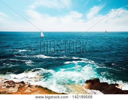 Summer Seascape with Transparent Clear Blue Water. Lighthouse and Sailing Yacht on Horizont. Sea Vacation Concept. Copy Space Background. Toned and Filtered Photo.