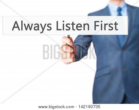 Always Listen First - Businessman Hand Holding Sign