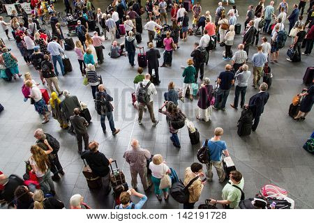 KING'S CROSS STATION, LONDON, UK - JULY 21, 2016. Looking down from above onto the crowded concourse of King's Cross Station in London during the peak time rush as rail passengers and commuters wait for information about their trains.