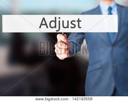 Adjust - Businessman Hand Holding Sign