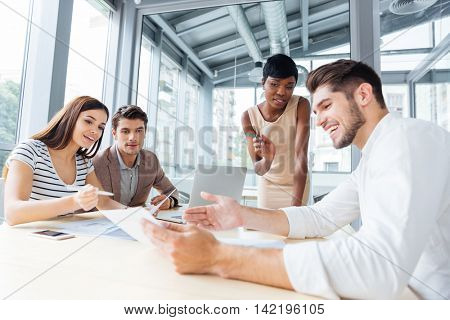 Group of enthusiastic cheerful colleagues discussing ideas and planning work in office