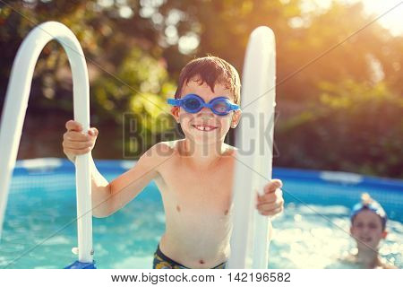 Little boy holding pools handrail outdoor in sunset childhood