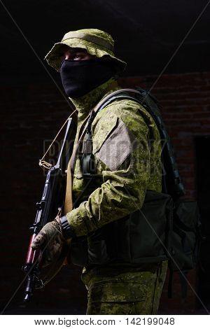 Man in uniform with mask and gun in hands on dark background