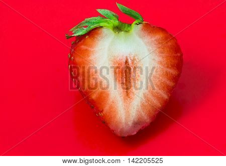 Cleaved single strawberry isolated on red background and clipping path