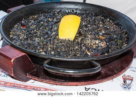 Arroz Negro black paella with seafood in a Paellera.