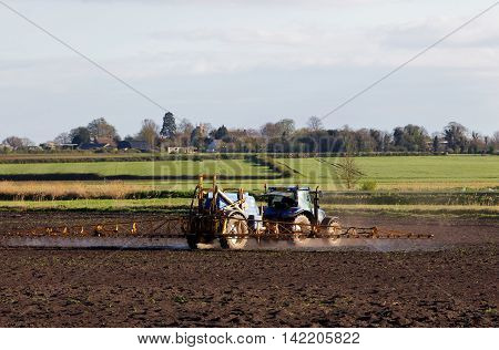 MARCH, UK - APRIL 22 : A crop sprayer applies fungicide to the young cereal plants on a bright spring day on April 22, 2015 in March. The UK grows around 16mn tonnes of wheat per annum