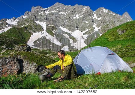 Young man preparing to eat on the burner near the tent in the mountains of Georgia