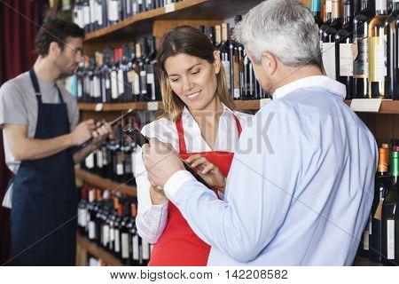 Saleswoman Reading Label Of Wine Bottle For Customer