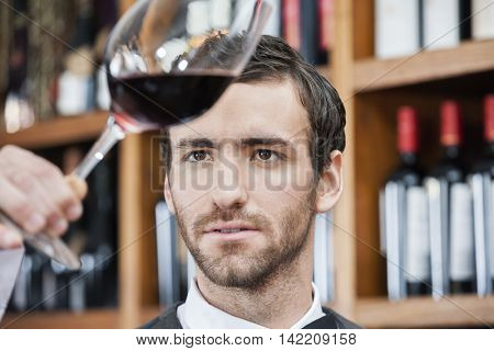 Bartender Examining Red Wine In Glass