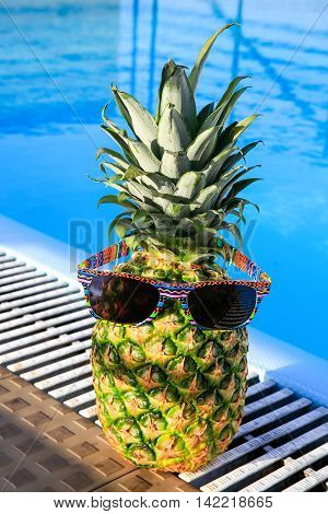 Pineapple wearing sunglasses at swimming pool on sunny day