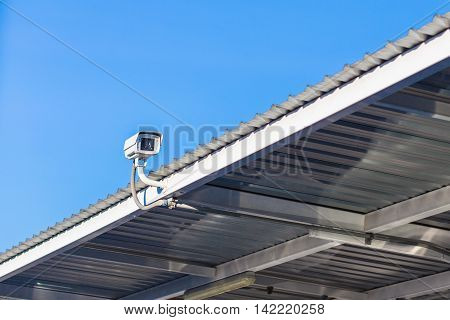 The close circuit camera on the roof with the blue sky background. The security system from the close-circuit camera.