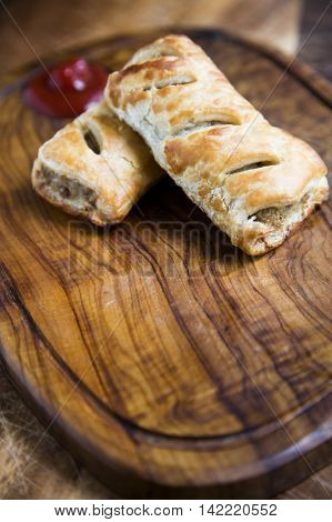 Traditional sausage rolls on wooden chopping board