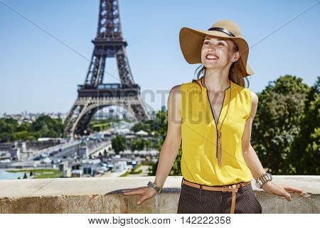 Happy Young Woman Looking Aside Against Eiffel Tower In Paris