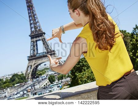Young Woman Framing With Hands In Front Of Eiffel Tower In Paris
