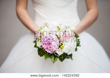 Beautiful pink peony wedding bouquet in bride's hands closeup selective focus