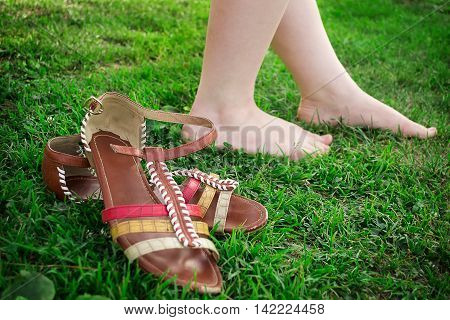 She took off her sandals and walks barefoot on the grass.