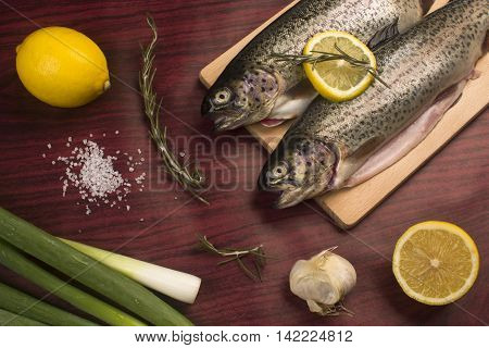 Raw trout fish with other food ingredients lemon rosemary garlic spring onion salt.