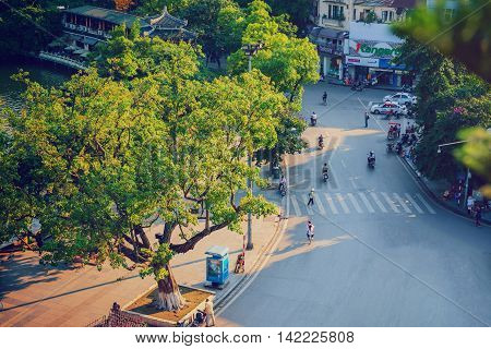 Hanoi,Vietnam - 09 May,2014: People go in the street in sunny afternoon day at Hoan Kiem lake
