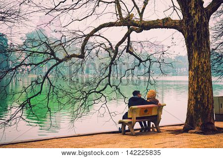 Hanoi, Vietnam - 11 March,2014: The couple sit on the bench at Hoan Kiem lake