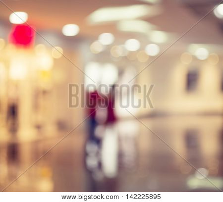 Blurred Background: people go for Shopping Mall along the window.