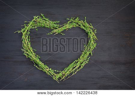 Fresh green thyme laid out in the shape of a heart
