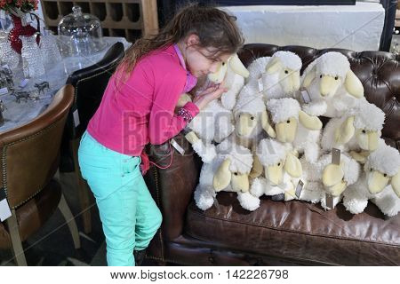teen girl and eleven soft toy white sheep on brown leather couch