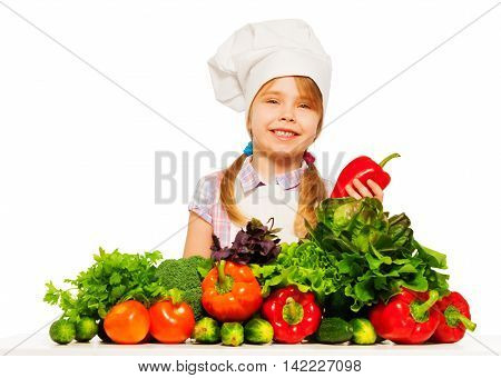 Smiling 6 years old little girl in cook's uniform holding fresh red pepper, isolated on white