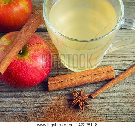 Cider juicy apples and cinnamon on old wooden background.