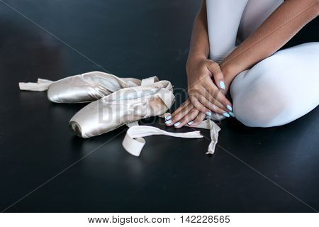 Hands of young ballet dancers touching the tape of her pointes