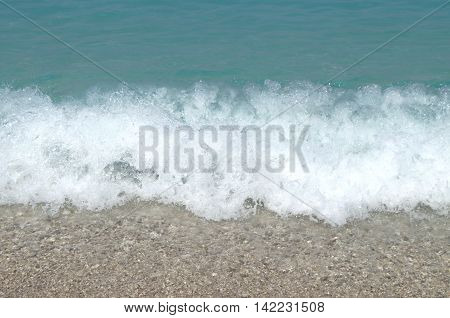 Sea time with white foamy waves on the beach