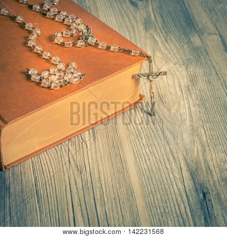 vintage rosary beads on old books square photo.
