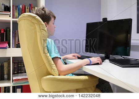 Teen boy sitting in chair at computer in his room and looking at monitor, side view