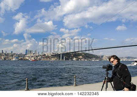 Istanbul Turkey - March 10 2013: Istanbul Strait views. A photographer landscape viewing. Against the European side of Istanbul coast visible in the background