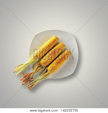 Whole Grilled Sweet Corn on a white plate and table from above