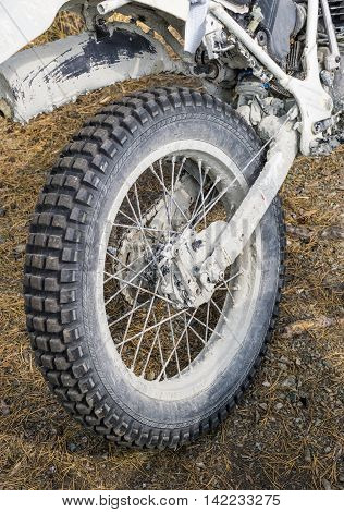 Rear motorcycle dirty wheel with enduro tire standing on old grass