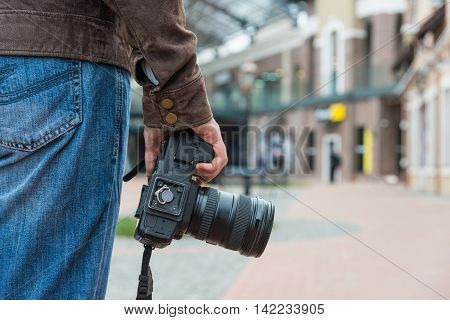 Photographer with camera in the city, hand holding camera close-up
