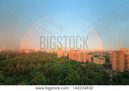 View of one of districts of city after storm, double rainbow.