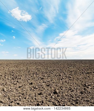 arable field and blue sky with clouds